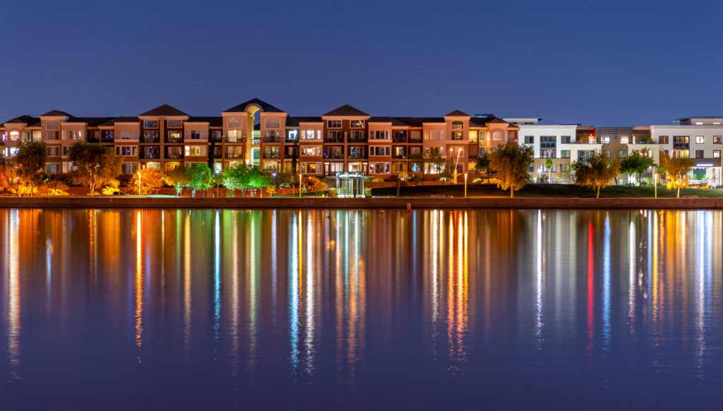 The multi-hued lights of stylish condos reflect off the calm waters of Tempe Town Lake in Tempe, Arizona.